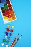 Χρώματα και βούρτσες Watercolor στο μπλε υπόβαθρο στοκ εικόνα με δικαίωμα ελεύθερης χρήσης