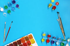 Χρώματα και βούρτσες Watercolor στο μπλε υπόβαθρο στοκ εικόνα