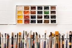 Χρώματα και πινέλα Watercolor για τη ζωγραφική στον ξύλινο πίνακα Στοκ Εικόνα