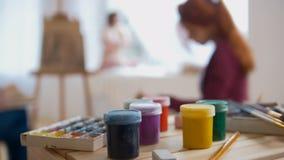 Χρώματα και προμήθειες τέχνης μπροστά από τους καλλιτέχνες την ώρα της παράστασης το καλλιτεχνικό γυμνό πρότυπο etude witn Στοκ εικόνες με δικαίωμα ελεύθερης χρήσης