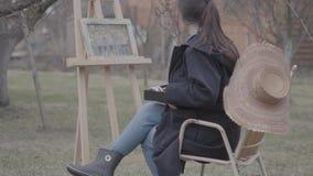 Χρώματα καλλιτεχνών πορτρέτου αρκετά επιτυχή στον καμβά στο κατώφλι Όμορφο ενθουσιώδες κορίτσι που συμμετέχεται απόθεμα βίντεο