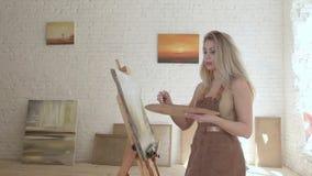 Χρώματα καλλιτεχνών κοριτσιών στον καμβά easel σε σε αργή κίνηση απόθεμα βίντεο