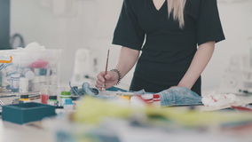Χρώματα σχεδιαστών γυναικών με τα ειδικά χρώματα και βούρτσες στο ύφασμα φιλμ μικρού μήκους
