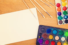 Χρώματα Watercolor, βούρτσες για τη ζωγραφική και κενό φύλλο της Λευκής Βίβλου στο ξύλινο υπόβαθρο Στοκ Εικόνες
