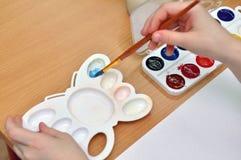 Χρώματα watercolor μιγμάτων παιδιών σε μια παλέτα Στοκ Εικόνες