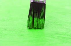 Χρώμα βουρτσών μια ξύλινη επιφάνεια ένα πράσινο υπόβαθρο Στοκ φωτογραφία με δικαίωμα ελεύθερης χρήσης