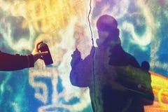 Χρώμα καλλιτεχνών γκράφιτι που ψεκάζει τον τοίχο Στοκ Φωτογραφίες