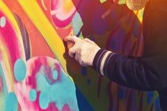 Χρώμα καλλιτεχνών γκράφιτι που ψεκάζει τον τοίχο Στοκ εικόνα με δικαίωμα ελεύθερης χρήσης
