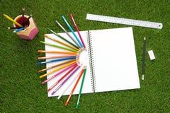 Χρώμα μολυβιών που τίθεται στην πράσινη χλόη στοκ εικόνες