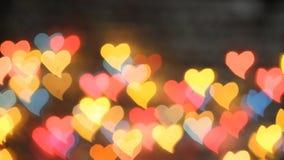 Χρώμα Bokeh σε ένα σκοτεινό υπόβαθρο με τις καρδιές απόθεμα βίντεο