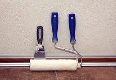 Χρώμα rollesr και trowel στάσεις σε ένα δωμάτιο στο baseboard κοντά στον τοίχο στοκ φωτογραφία