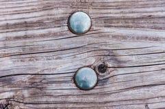 Χρώμιο γύρω από τα κεφάλια από μια βίδα σε έναν ξύλινο πίνακα στοκ εικόνα με δικαίωμα ελεύθερης χρήσης