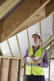 Χτίζοντας επιθεωρητής που εξετάζει τη στέγη της νέας ιδιοκτησίας Στοκ φωτογραφία με δικαίωμα ελεύθερης χρήσης