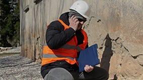 Χτίζοντας επιθεωρητής που μιλά στο τηλέφωνο κυττάρων κοντά στον παλαιό τοίχο απόθεμα βίντεο