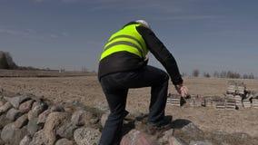 Χτίζοντας επιθεωρητής που χρησιμοποιεί την ταμπλέτα κοντά στον τοίχο πετρών απόθεμα βίντεο