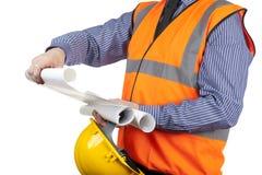 Χτίζοντας επιθεωρητής στην πορτοκαλιά φανέλλα διαφάνειας που ελέγχει τα σχέδια κατασκευής Στοκ εικόνα με δικαίωμα ελεύθερης χρήσης