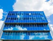 χτίζοντας την πρόσοψη σύγχρ&o Τα παράθυρα γυαλιού απεικόνισαν τον ουρανό και τα σύννεφα μπλε γάμμα Στοκ φωτογραφία με δικαίωμα ελεύθερης χρήσης