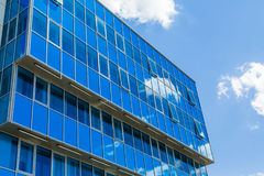 χτίζοντας την πρόσοψη σύγχρ&o Τα παράθυρα γυαλιού απεικόνισαν τον ουρανό και τα σύννεφα μπλε γάμμα Στοκ εικόνα με δικαίωμα ελεύθερης χρήσης