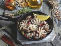 Χταπόδι μωρών που μαγειρεύεται, ψημένος στην παν μερίδα σιδήρου, με το λεμόνι και στενό επάνω καρυκευμάτων στοκ εικόνες