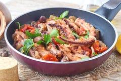 Χταπόδι που μαγειρεύεται στο ελαιόλαδο με τις ελιές, oregano, ντομάτες, κάπαρες, λεμόνι σε ένα τηγανίζοντας τηγάνι κατανάλωση υγι Στοκ εικόνες με δικαίωμα ελεύθερης χρήσης