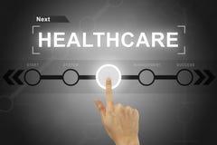 Χτυπώντας κουμπί υγειονομικής περίθαλψης χεριών σε μια διεπαφή οθόνης Στοκ Φωτογραφίες