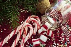 /Χυμένος από τις γλυκές καραμέλες βάζων γυαλιού στην κόκκινη ΤΣΕ Χριστουγέννων Στοκ Φωτογραφία