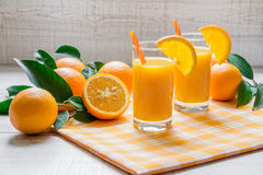 2 χυμοί από πορτοκάλι με τις πορτοκαλιές φέτες, άχυρα Στοκ Φωτογραφίες