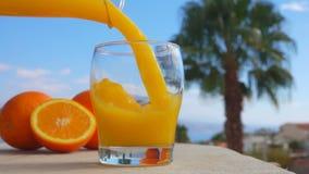 Χυμός από πορτοκάλι κινηματογραφήσεων σε πρώτο πλάνο που χύνεται σε ένα γυαλί απόθεμα βίντεο