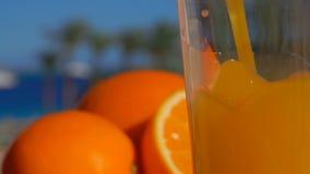 Χυμός από πορτοκάλι κινηματογραφήσεων σε πρώτο πλάνο που χύνεται σε ένα γυαλί φιλμ μικρού μήκους