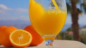 Χυμός από πορτοκάλι κινηματογραφήσεων σε πρώτο πλάνο που χύνεται wine-glass απόθεμα βίντεο