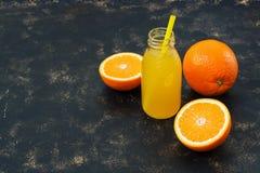 Χυμός από πορτοκάλι σε ένα μπουκάλι και μισό πορτοκάλι σε ένα σκοτεινό υπόβαθρο Στοκ φωτογραφία με δικαίωμα ελεύθερης χρήσης