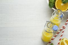 Χυμός από πορτοκάλι στα μπουκάλια και τα πορτοκάλια σε ένα άσπρο υπόβαθρο Στοκ Εικόνες
