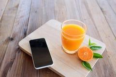 Χυμός από πορτοκάλι στο ξύλινο υπόβαθρο στοκ φωτογραφίες