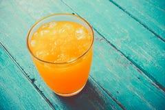 χυμός από πορτοκάλι τοπ άποψης στο γυαλί με τον πάγο στο ωκεάνιο μπλε ξύλινο ποσό Στοκ εικόνα με δικαίωμα ελεύθερης χρήσης