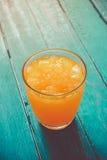 χυμός από πορτοκάλι τοπ άποψης στο γυαλί με τον πάγο στο ωκεάνιο μπλε ξύλινο ποσό Στοκ Εικόνες