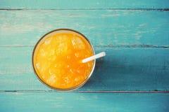 χυμός από πορτοκάλι τοπ άποψης στο γυαλί με τον πάγο στο ωκεάνιο μπλε ξύλινο ποσό Στοκ Εικόνα