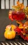 Χυμός και γεμισμένο καραμέλα γυαλί κρασιού με το φύλλωμα φθινοπώρου Στοκ Φωτογραφίες