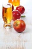 Χυμός και μήλα της Apple σε έναν ξύλινο πίνακα Στοκ Φωτογραφίες