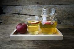 Χυμός και μήλα της Apple σε έναν ξύλινο πίνακα Στοκ Εικόνα