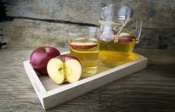Χυμός και μήλα της Apple σε έναν ξύλινο πίνακα Στοκ Φωτογραφία