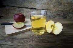 Χυμός και μήλα της Apple σε έναν ξύλινο πίνακα Στοκ Εικόνες