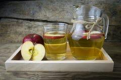 Χυμός και μήλα της Apple σε έναν ξύλινο πίνακα Στοκ εικόνα με δικαίωμα ελεύθερης χρήσης