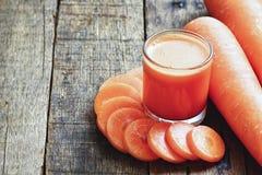 Χυμός καρότων και φέτες καρότων στον ξύλινο πίνακα Στοκ φωτογραφίες με δικαίωμα ελεύθερης χρήσης