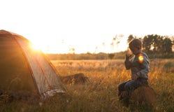 Χυμός κατανάλωσης αγοριών στο ηλιοβασίλεμα, συνεδρίαση αγοριών κοντά στη σκηνή Στοκ εικόνες με δικαίωμα ελεύθερης χρήσης