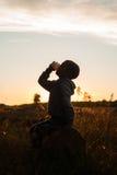 Χυμός κατανάλωσης αγοριών στο ηλιοβασίλεμα, συνεδρίαση αγοριών κοντά στη σκηνή Στοκ Εικόνες