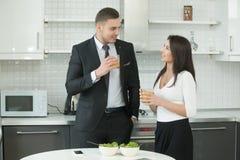 Χυμός κατανάλωσης ανδρών και γυναικών στην κουζίνα στοκ φωτογραφίες