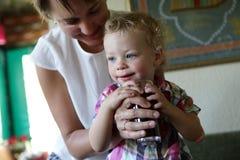 Χυμός κατανάλωσης γιων από τα χέρια μητέρων του στοκ εικόνα με δικαίωμα ελεύθερης χρήσης