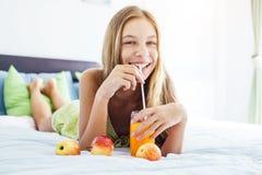 Χυμός κατανάλωσης κοριτσιών και χαλάρωση στην κρεβατοκάμαρα Στοκ Εικόνες