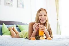 Χυμός κατανάλωσης κοριτσιών και χαλάρωση στην κρεβατοκάμαρα Στοκ Εικόνα
