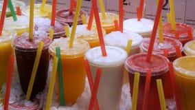 Χυμός καταφερτζήδων ή φρέσκος στα πλαστικά φλυτζάνια με τα χρωματισμένα άχυρα στο μετρητή της αγοράς φρούτων απόθεμα βίντεο